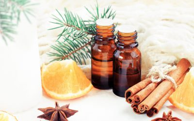 Relaxing winter season Essential oils blend. Dark glass bottles, cinnamon, orange, pine twigs, anise, woolen cloth. Natural home deodorants. White soft background.